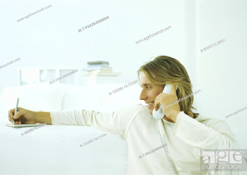 Stock Photo: Young man holding landline phone to ear, taking notes on notepad.