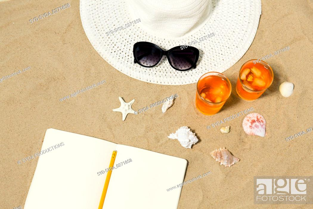 Stock Photo: notebook, cocktails, hat and shades on beach sand.