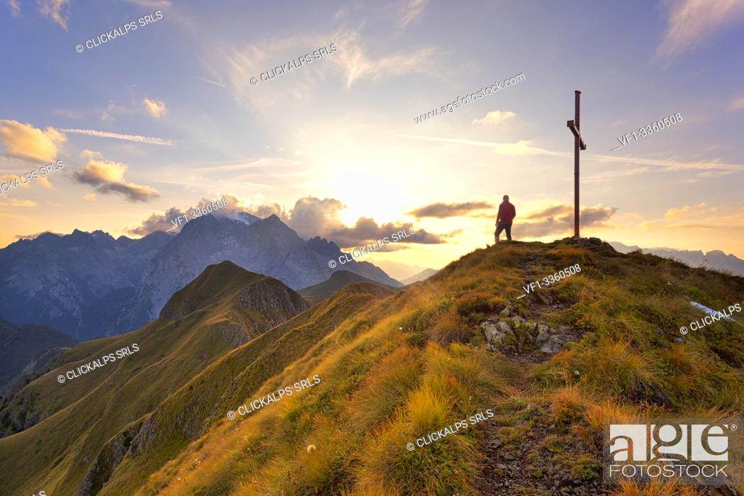 Stock Photo: A hiker admires the sunset on Marmolada group from the grassy summit of Migogn Mount, Dolomites, Marmolada group, Rocca Pietore, Belluno province, Veneto, Italy.