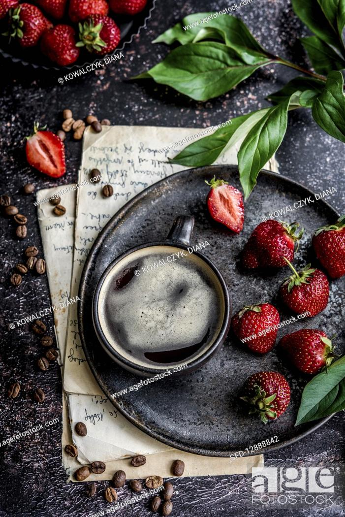 Stock Photo: Cup of coffee on a serving plate, strawberries beside it.