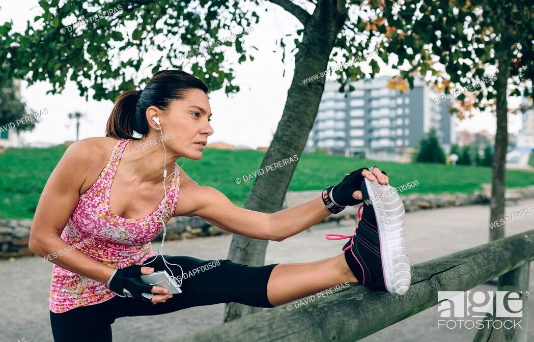 Stock Photo: Woman stretching in a park.