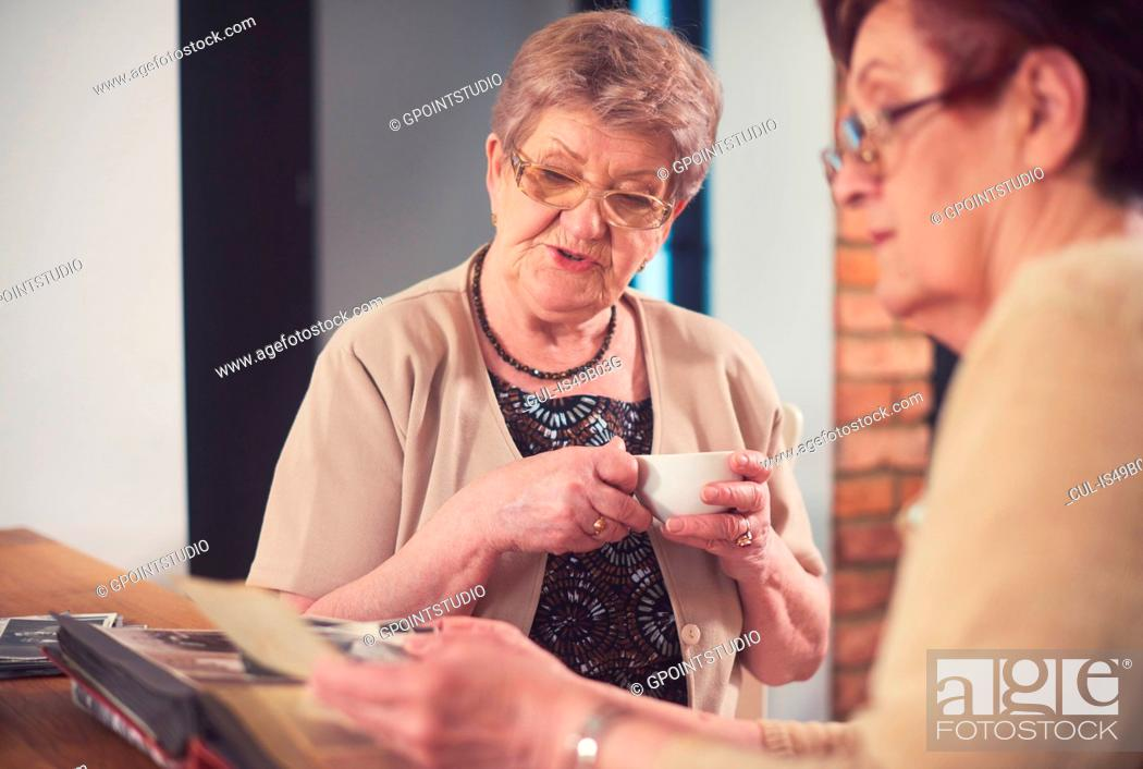 Stock Photo: Two senior women looking at old photographs at table.