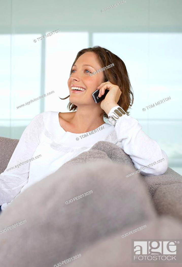 Stock Photo: Woman talking on cell phone on sofa smiling.