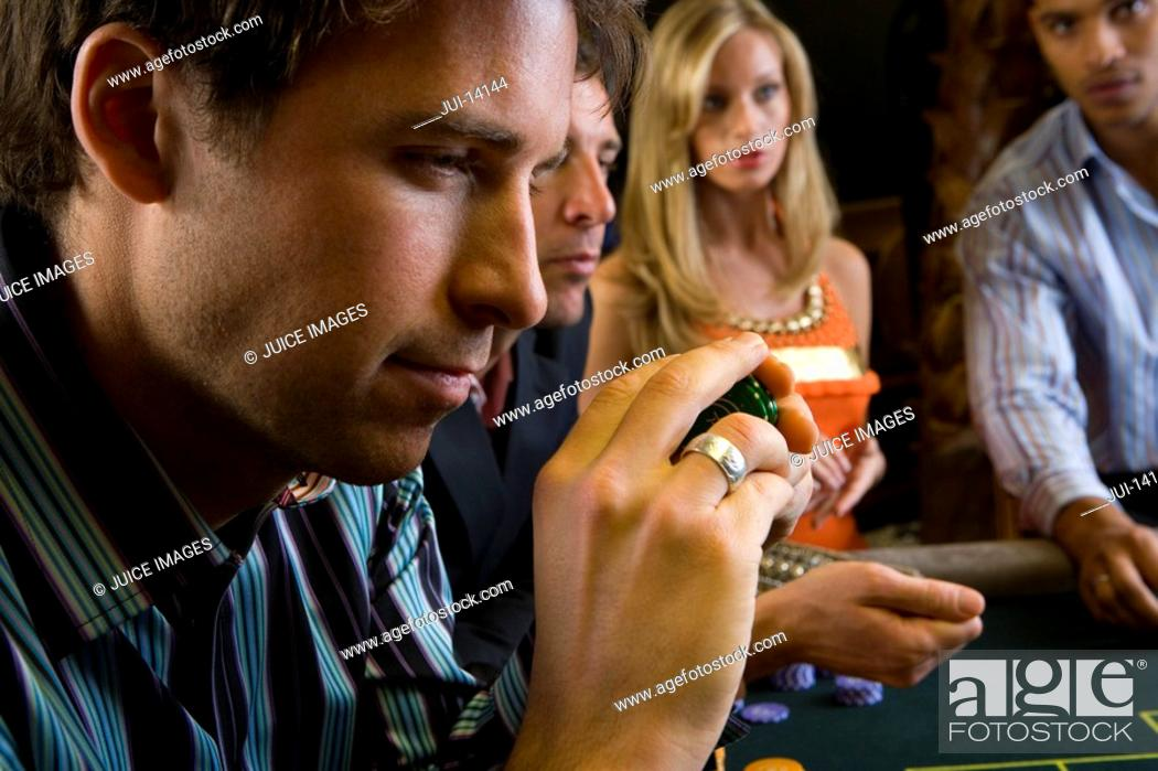 Stock Photo: Man with gambling chips at table, side view.