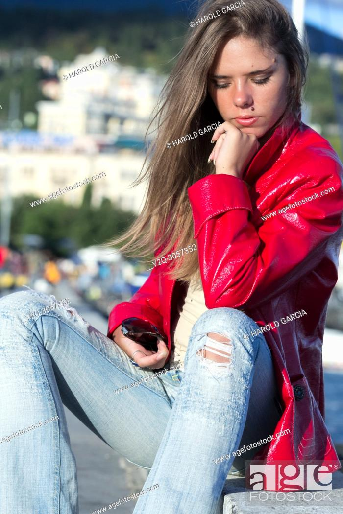Imagen: Beautiful woman in red jacket and jeans posing for the camera in different sensual positions in Yalta, Crimea.
