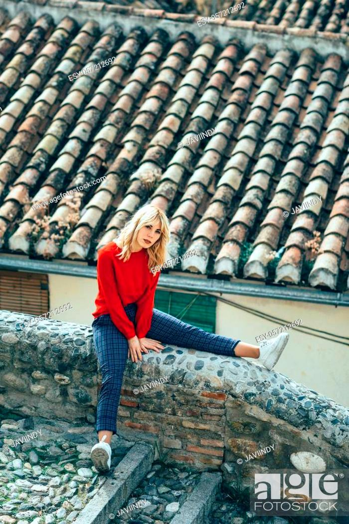 Stock Photo: Young blond woman sitting near beautiful roofs of charming old houses.. Smiling blonde girl with red shirt enjoying life outdoors.