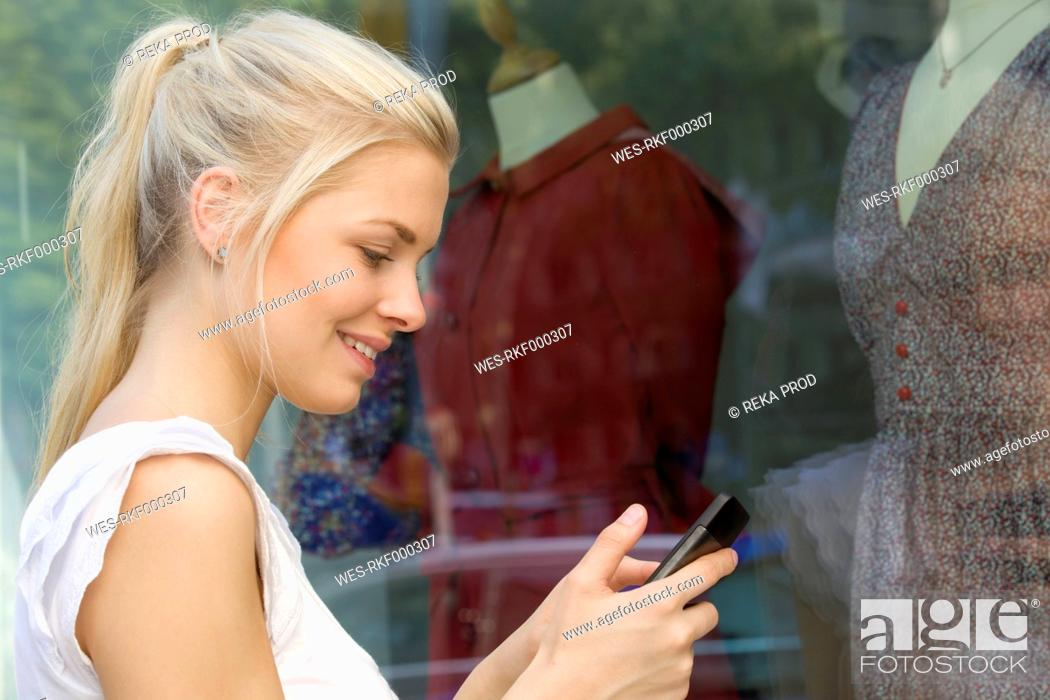Stock Photo: Germany, North Rhine Westphalia, Cologne, Young woman at window shopping with smart phone.