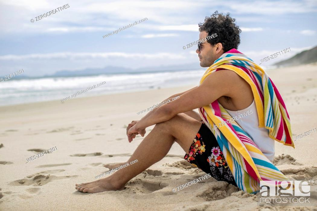 Stock Photo: Young man sitting on the beach.