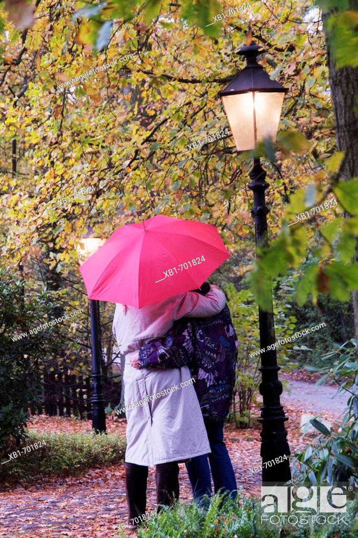 Stock Photo: Middleaged couple with an umbrella goes for a walk in rainy weather.