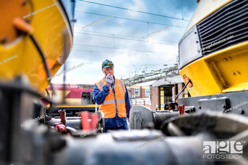 Stock Photo: Engineer using walkie-talkie to guide locomotive.