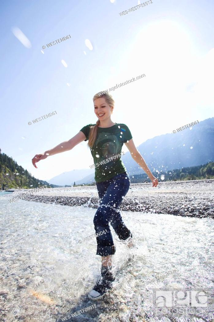 Stock Photo: Germany, Bavaria, Tölzer Land, Young woman running through river, smiling.