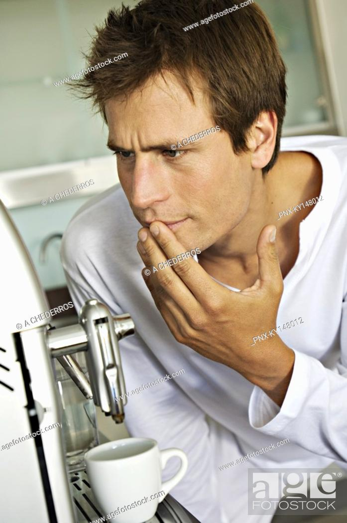 Stock Photo: Young man in front of espresso maker.
