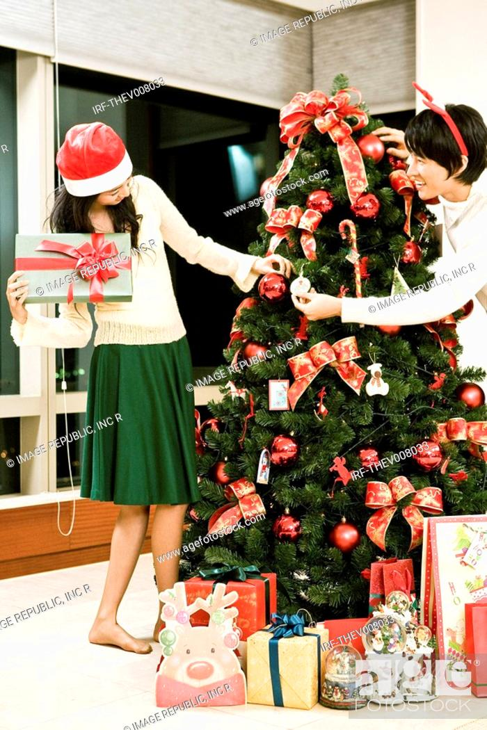 Stock Photo: young man and woman with the Christmas tree and gift boxes.