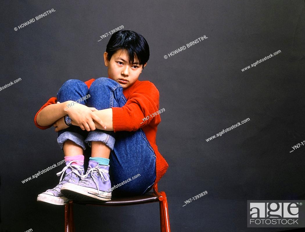 Stock Photo: Studio image of a an Asian teenage girl sitting on a chair clasping her knees and looking forlorn.