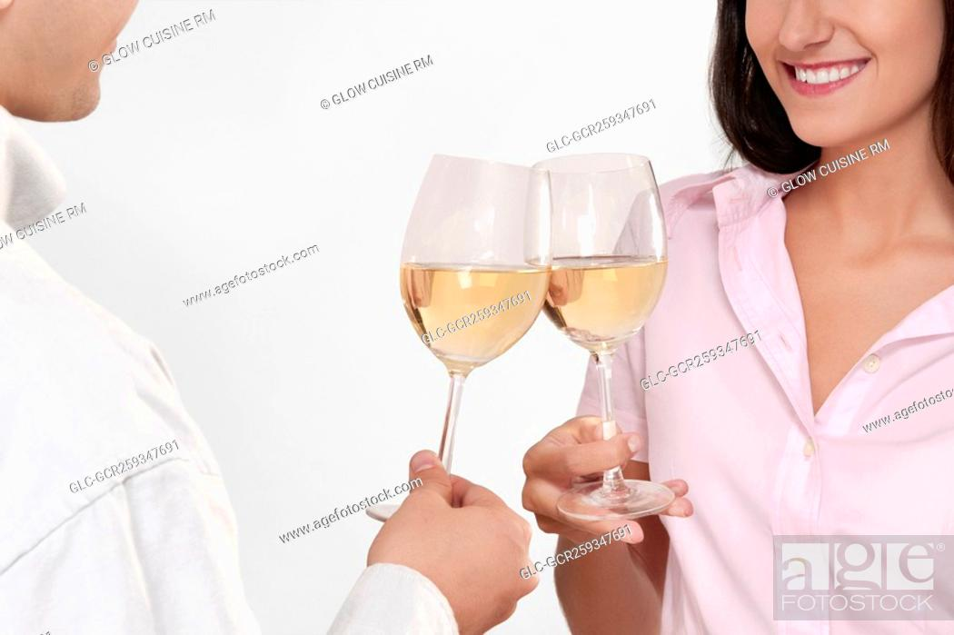 Imagen: Couple toasting glasses of wine and smiling.