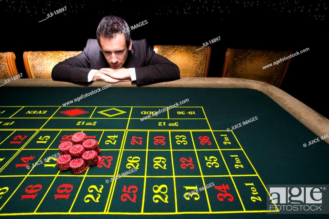 Stock Photo: Businessman looking at pile of gambling chips on roulette table.