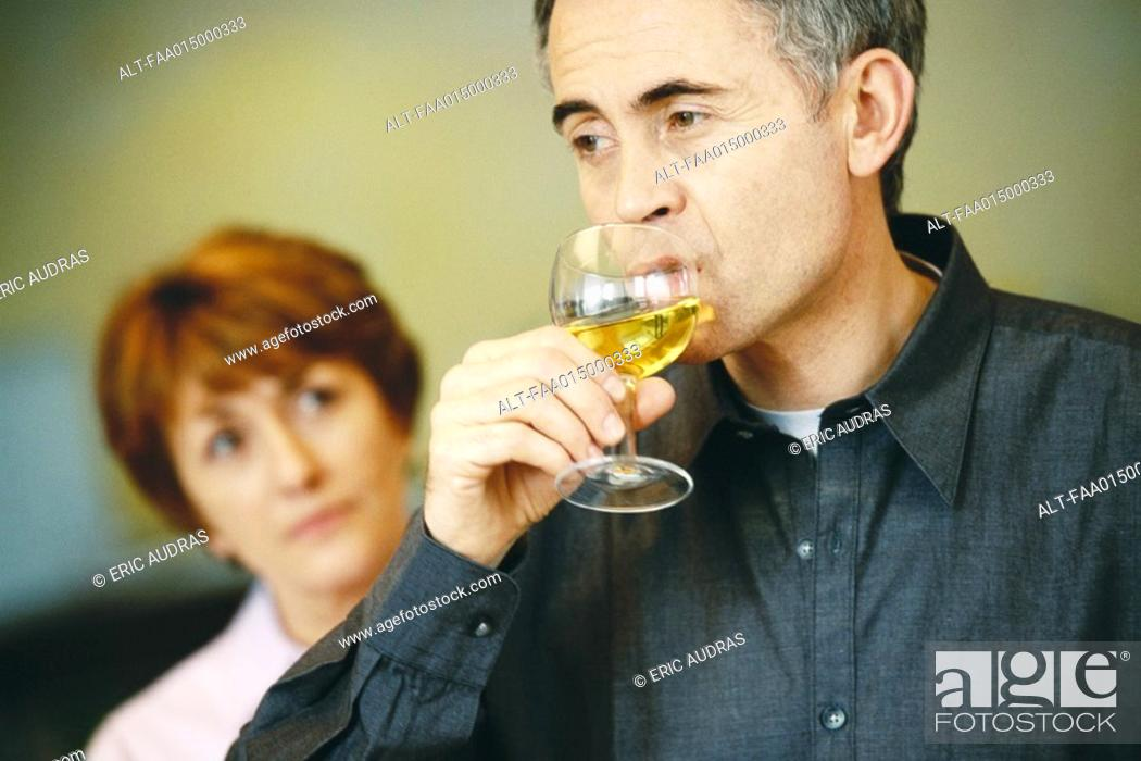 Stock Photo: Senior man drinking glass of wine, senior woman looking at him in background.