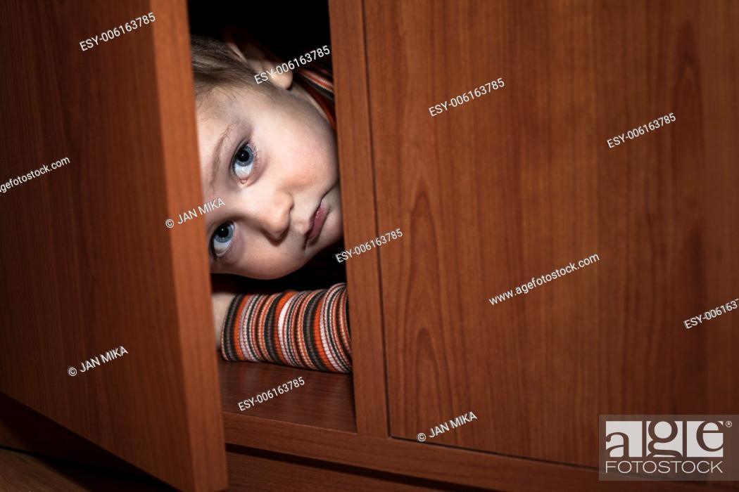 Stock Photo: Scared child boy hiding in wardrobe.