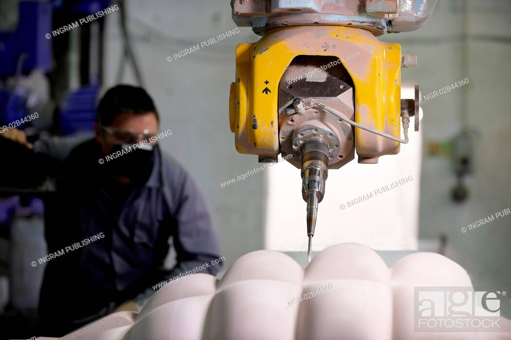 Stock Photo: worker controlling a multi axis milling machine.