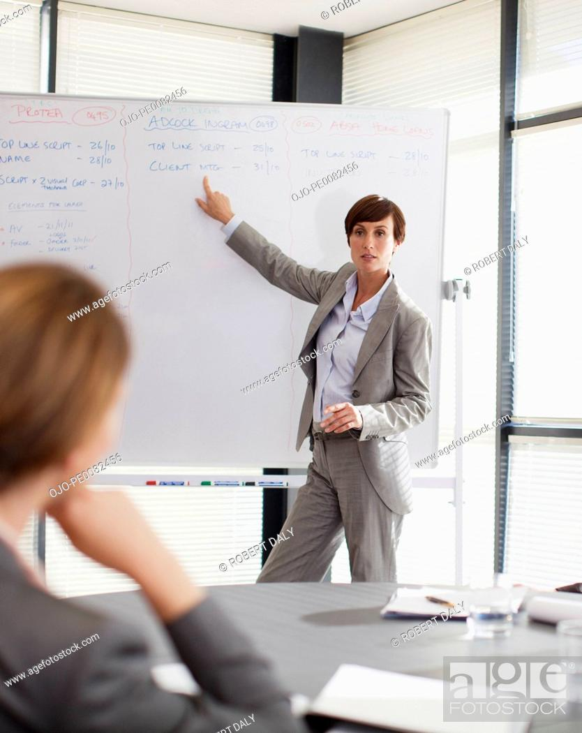 Stock Photo: Businesswoman at whiteboard presenting to co-workers.
