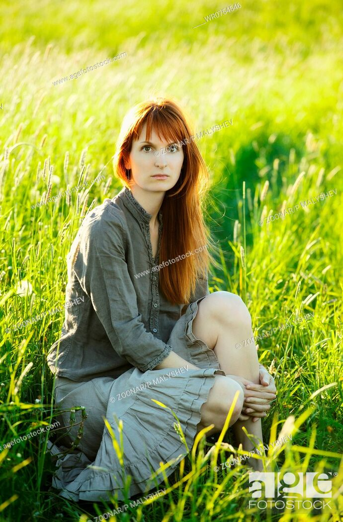 Stock Photo: sad redhead woman in grass.