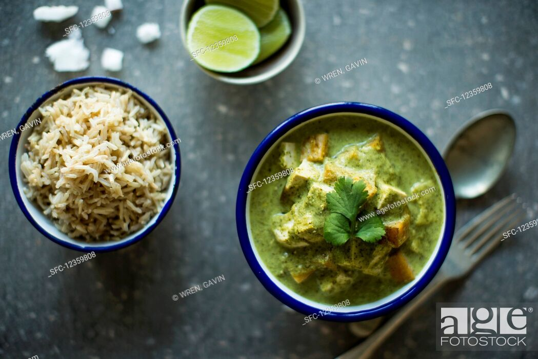 Stock Photo: Enamel bowls of vegetarian sweet potato and tofu thai curry with steamed rice, lime slices and coconut.