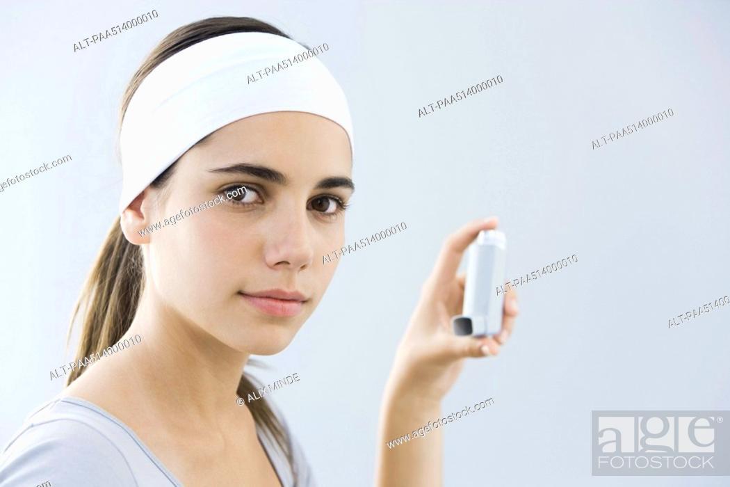 Stock Photo: Teen girl holding inhaler, looking at camera.