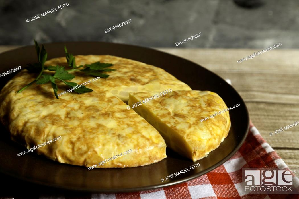 Stock Photo: Spanish omelette and portion in a plate with napkin on wooden table and dark background.