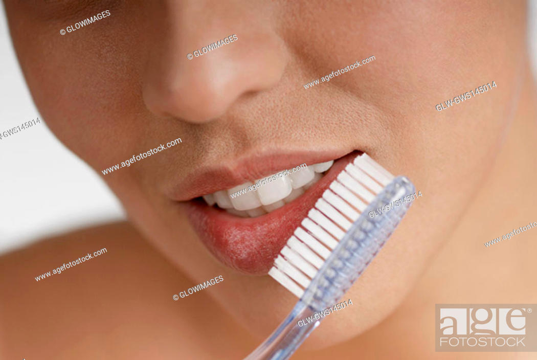Stock Photo: Close-up of a young woman brushing her teeth.