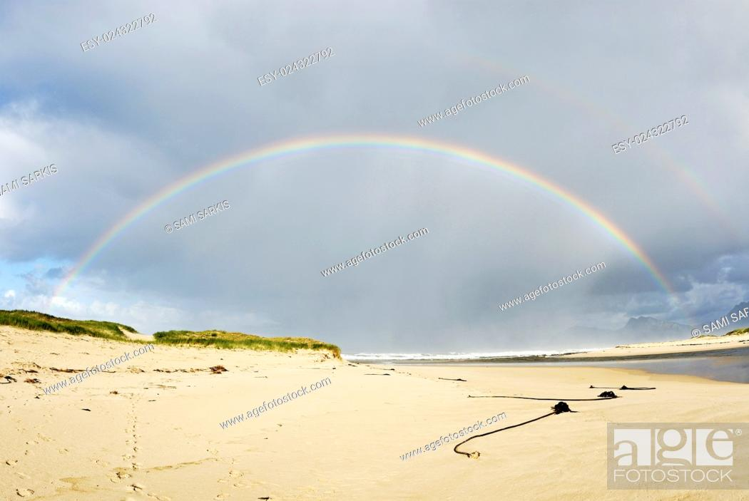Stock Photo: Beach and rainbow on a cloudy day, Hermanus, South Africa.