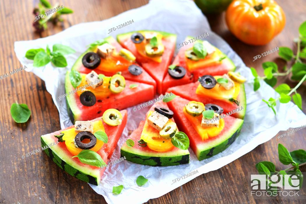 Stock Photo: Melon pieces garnished like a pizza with tomatoes, tofu, olives and fresh herbs.