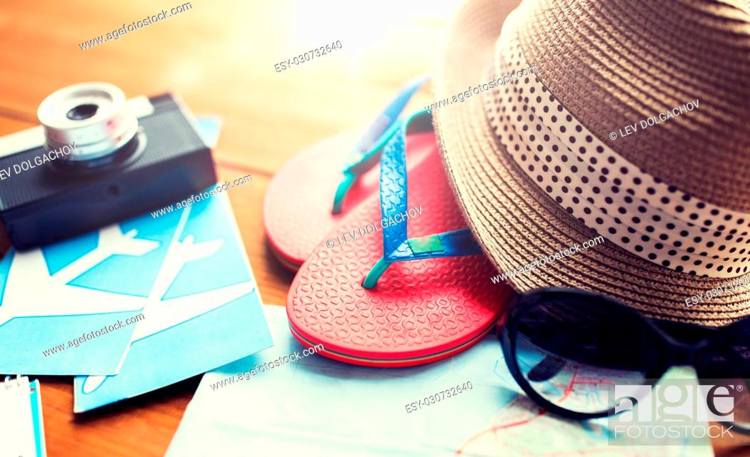 Stock Photo: summer vacation, tourism and objects concept - close up of travel map, flip-flops, hat and camera with airplane tickets on wooden table at home.