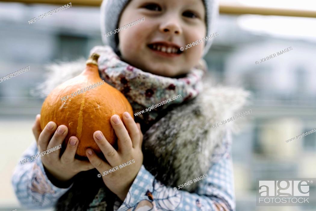 Stock Photo: Boy holding pumpkin outdoors.