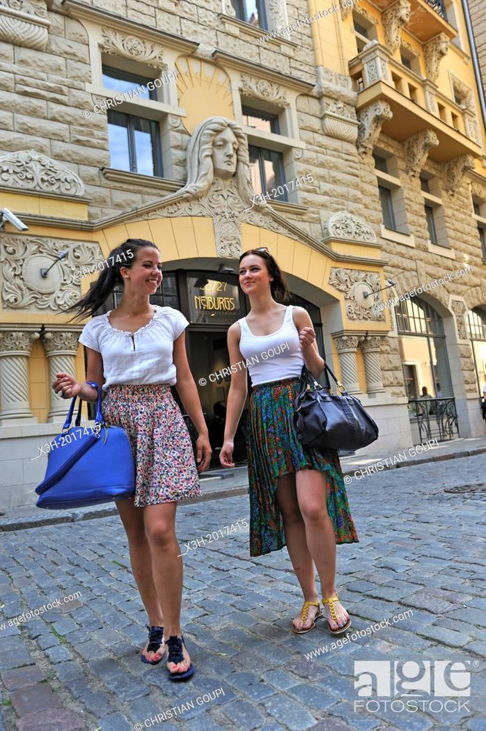 Stock Photo: two young girls walking in front of the facade of the Art Nouveau building housing the Neiburgs hotel, Riga, Latvia, Baltic region, Northern Europe.