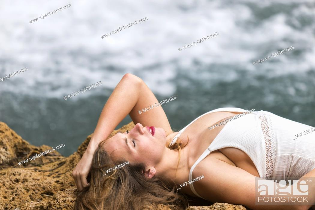 Imagen: Woman lying on the rock by the river wearing a white swimsuit.