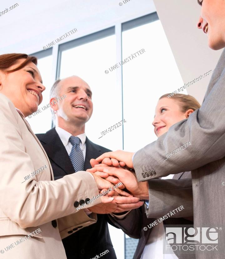 Stock Photo: Successful business team putting their hands on top of one another.