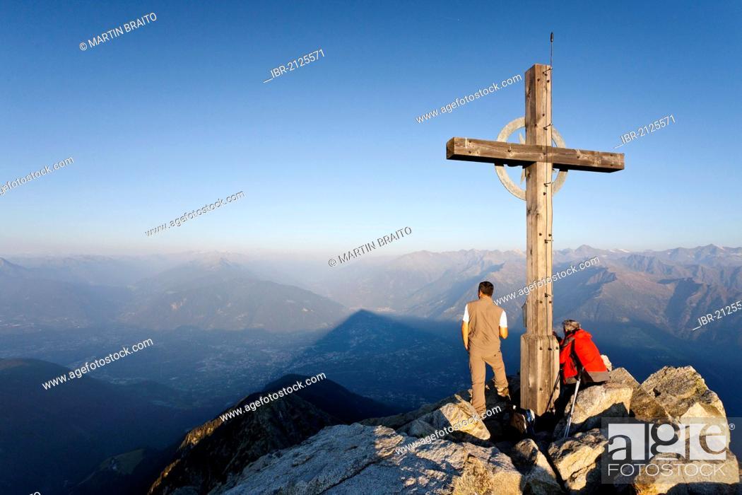 Stock Photo: Climber at sunrise at the summit cross of Ifingers Mountain above Meran, Meran 2000, Alto Adige, Italy, Europe.