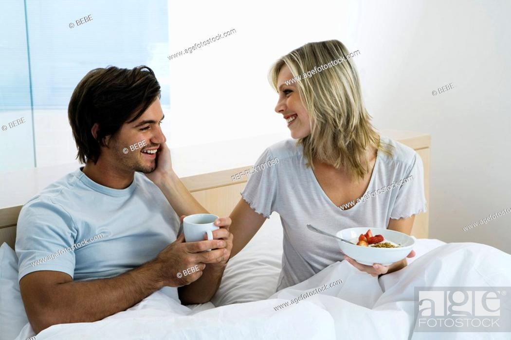 Stock Photo: Young couple sitting on bed, smiling, eating breakfast, drinking coffee.