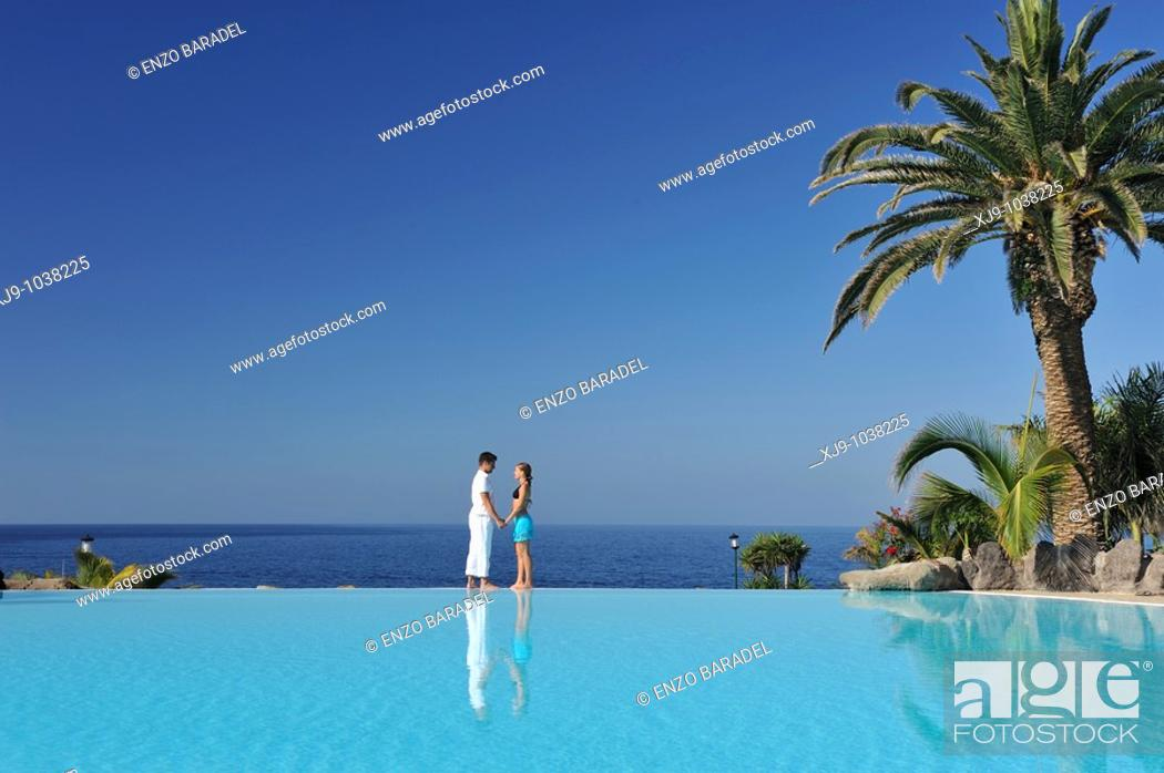 Stock Photo: Love face to face with infinity pool reflection.