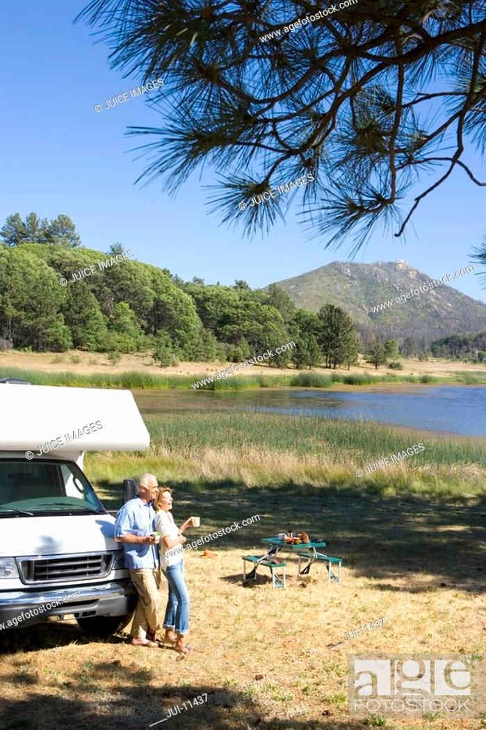 Stock Photo: Couple by motor home by lake, elevated view.