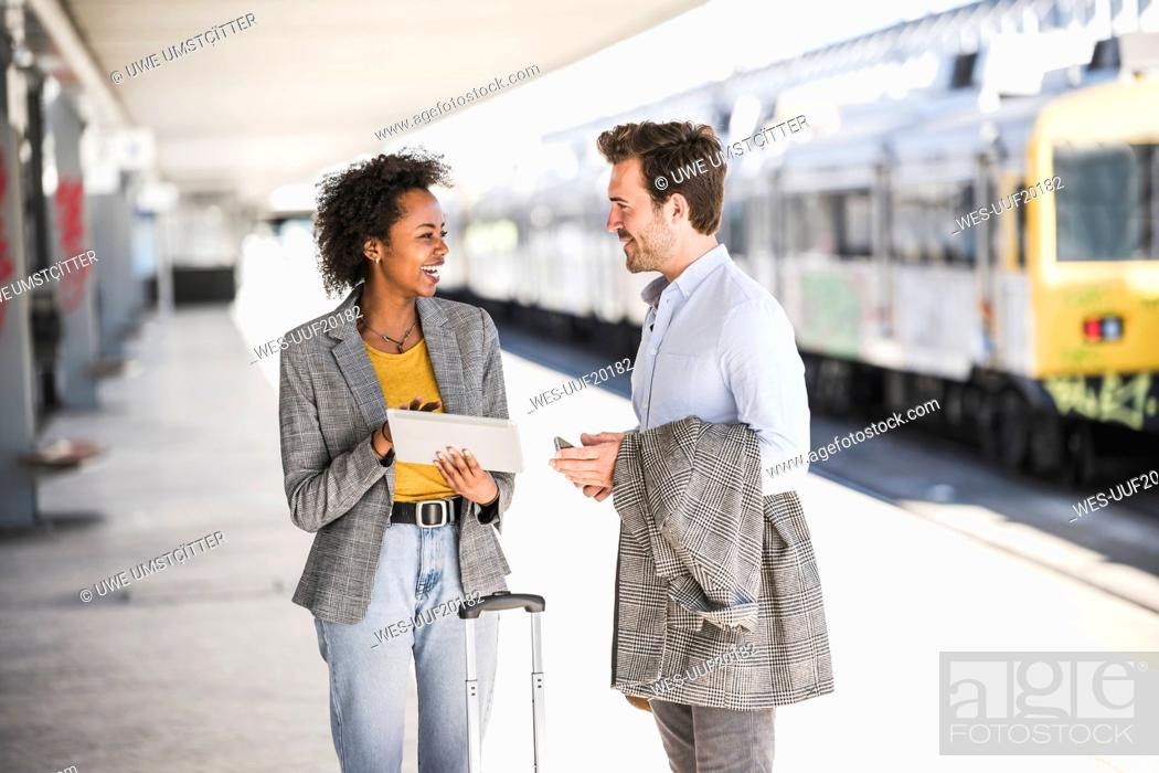 Stock Photo: Young businessman and happy businesswoman using tablet together at the train station.