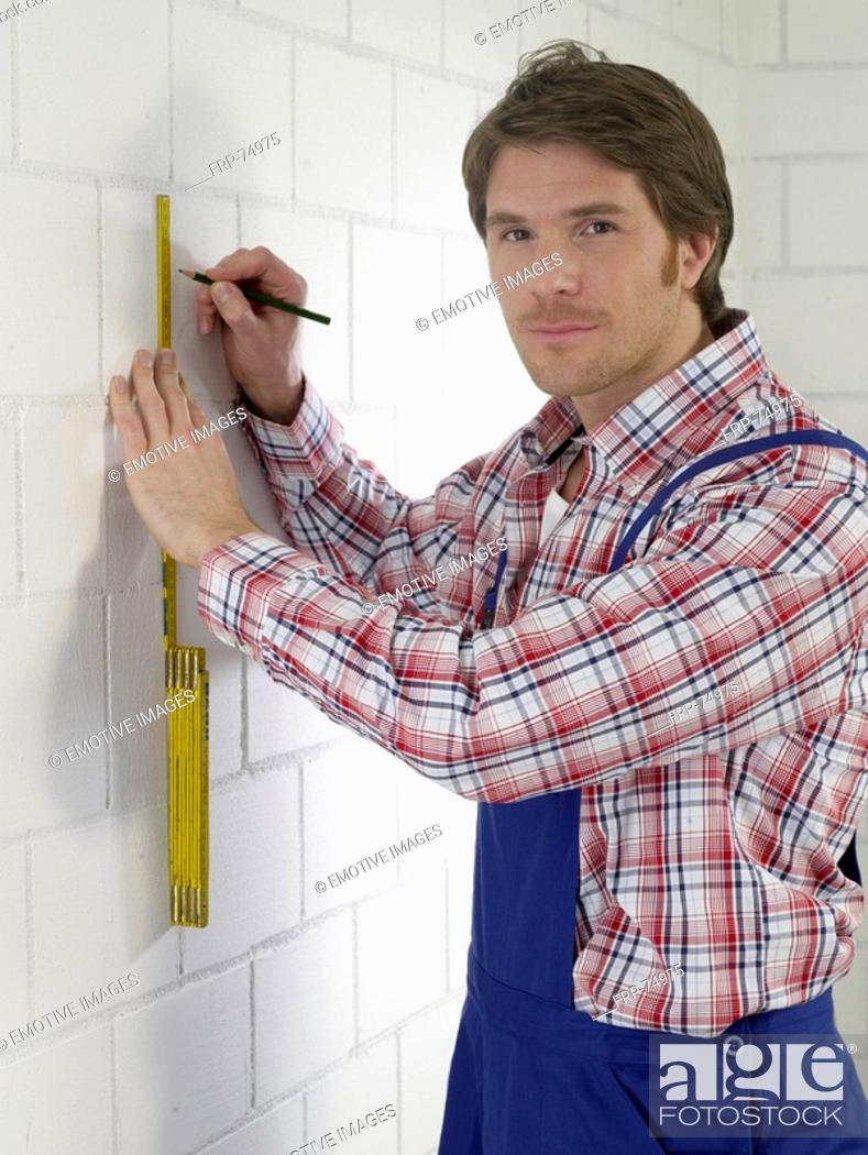 Stock Photo: Man wearing work wear with pencil and folding rule.