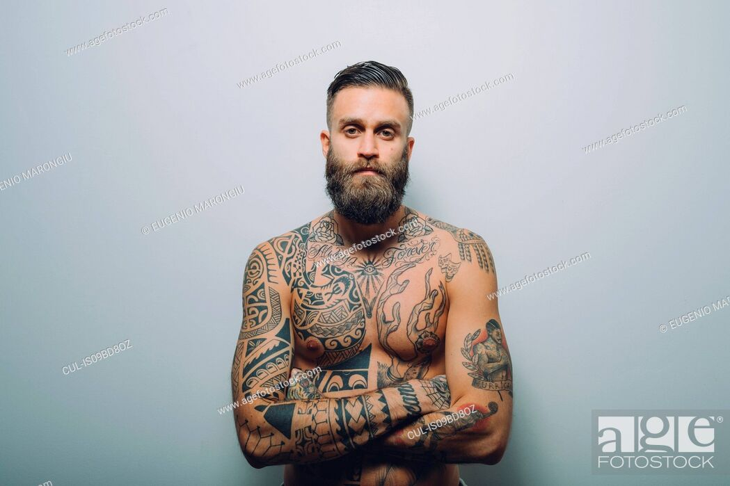 Stock Photo: Portrait of young man with beard, bare chest covered in tattoos, arms folded.