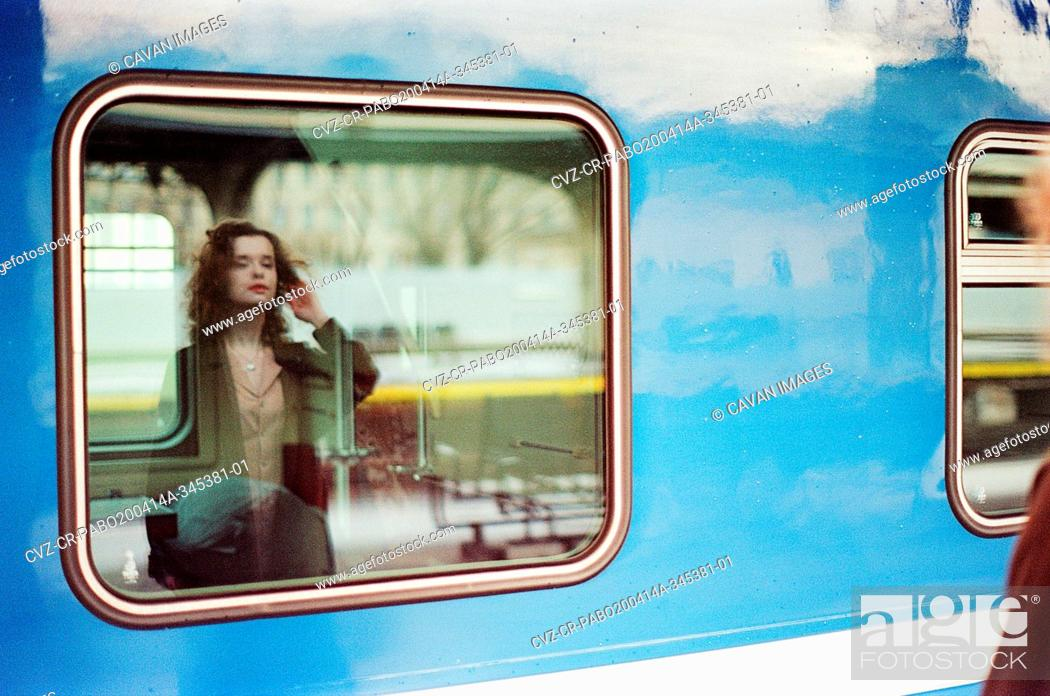 Stock Photo: A woman stands near a train at a train station.