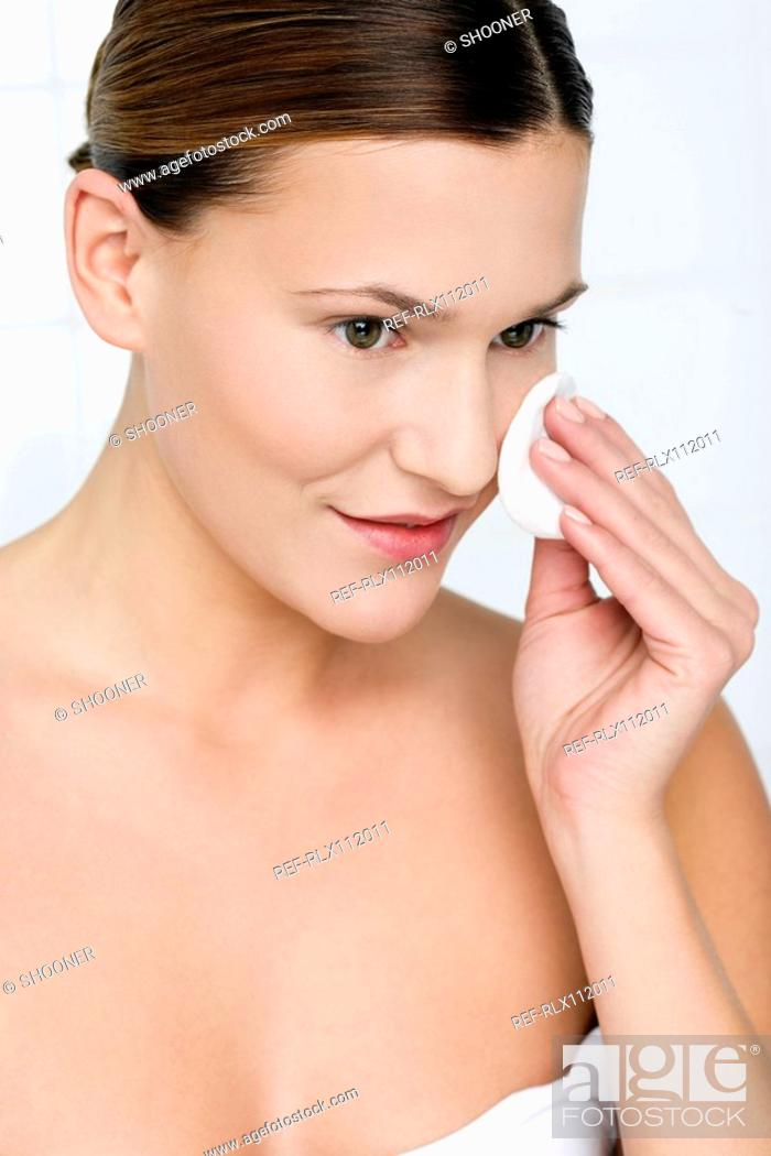 Stock Photo: Young woman removing make up.