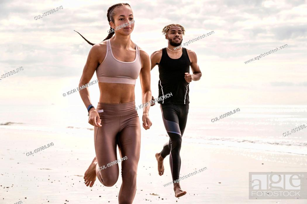 Stock Photo: Young male and female runners running barefoot along beach.