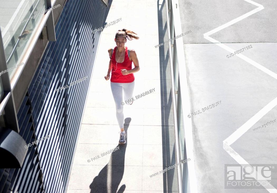 Stock Photo: Woman running on urban sidewalk.