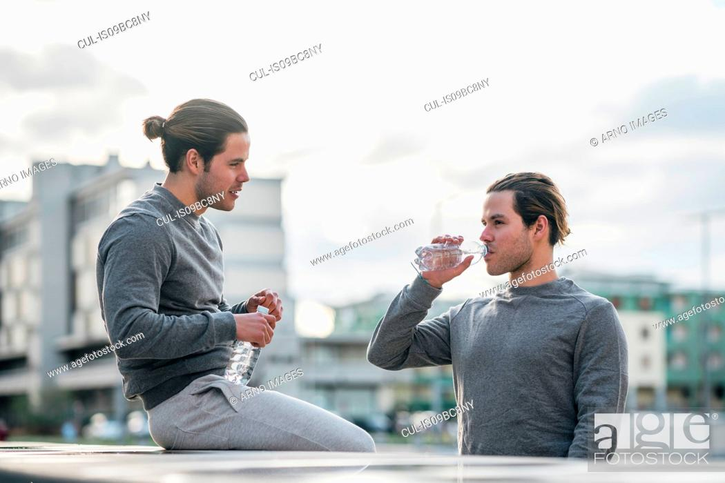 Imagen: Young adult male twins taking a training break, drinking water.
