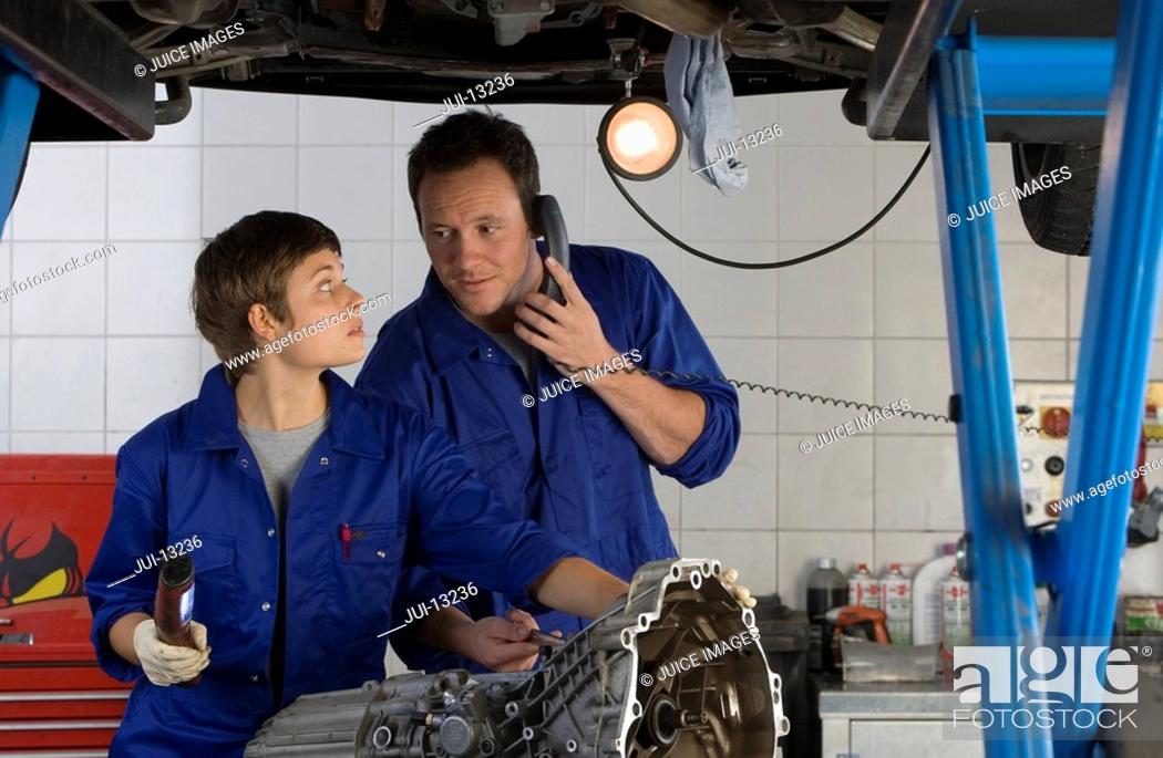 Stock Photo: Female mechanic looking at colleague on telephone by engine of elevated car.