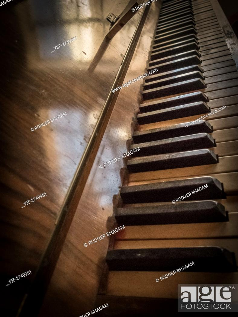 Stock Photo: An old batered piano, discarded and covered in dust.